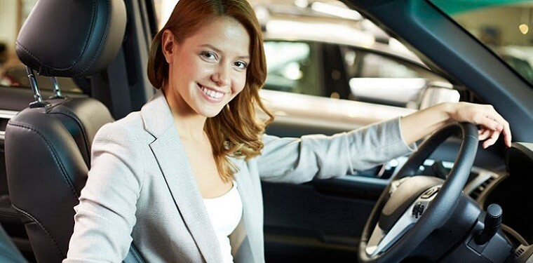Photo of elegant woman sitting in a new car in automobile center